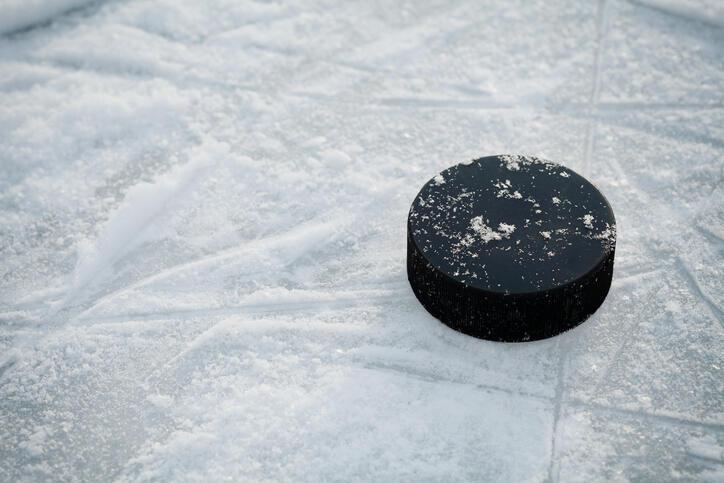 Hockey puck on ice hockey rink on shiny winter day