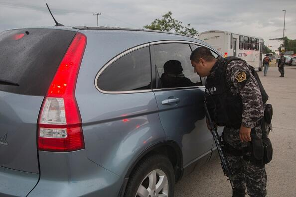 A state police officer inspects a vehicle at a checkpoint during a security operation  in Puerto Vallarta in the western Mexican state of Jalisco on August 17, 2016.  Jesus Alfredo Guzman Salazar, the son of drug lord Joaquin