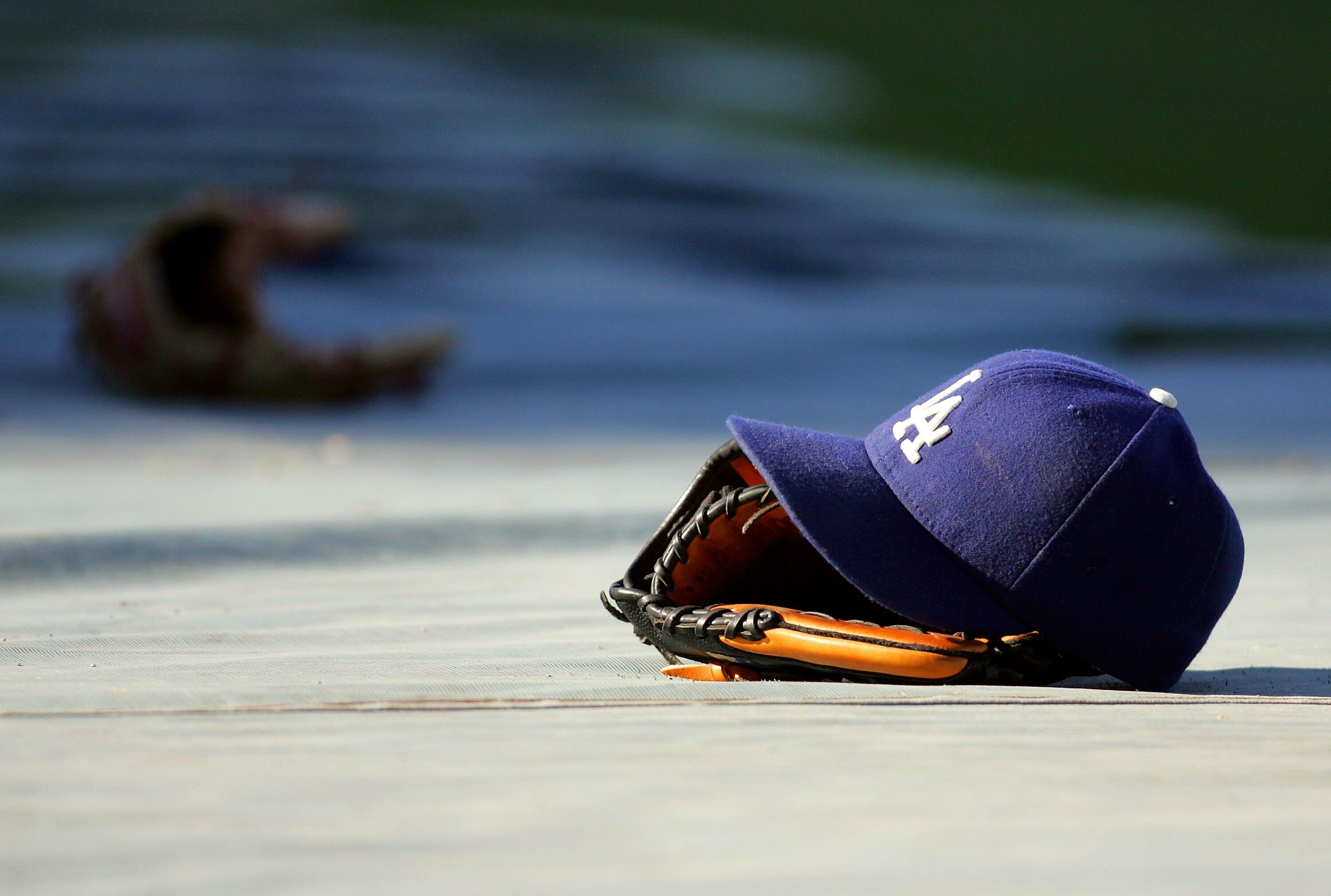 LOS ANGELES, CA - AUGUST 19:  A glove and a Los Angeles Dodgers cap lay on the tarp during batting practice prior to the MLB game against the Colorado Rockies at Dodger Stadium on August 19, 2008 in Los Angeles, California. The Rockies defeated the Dodger