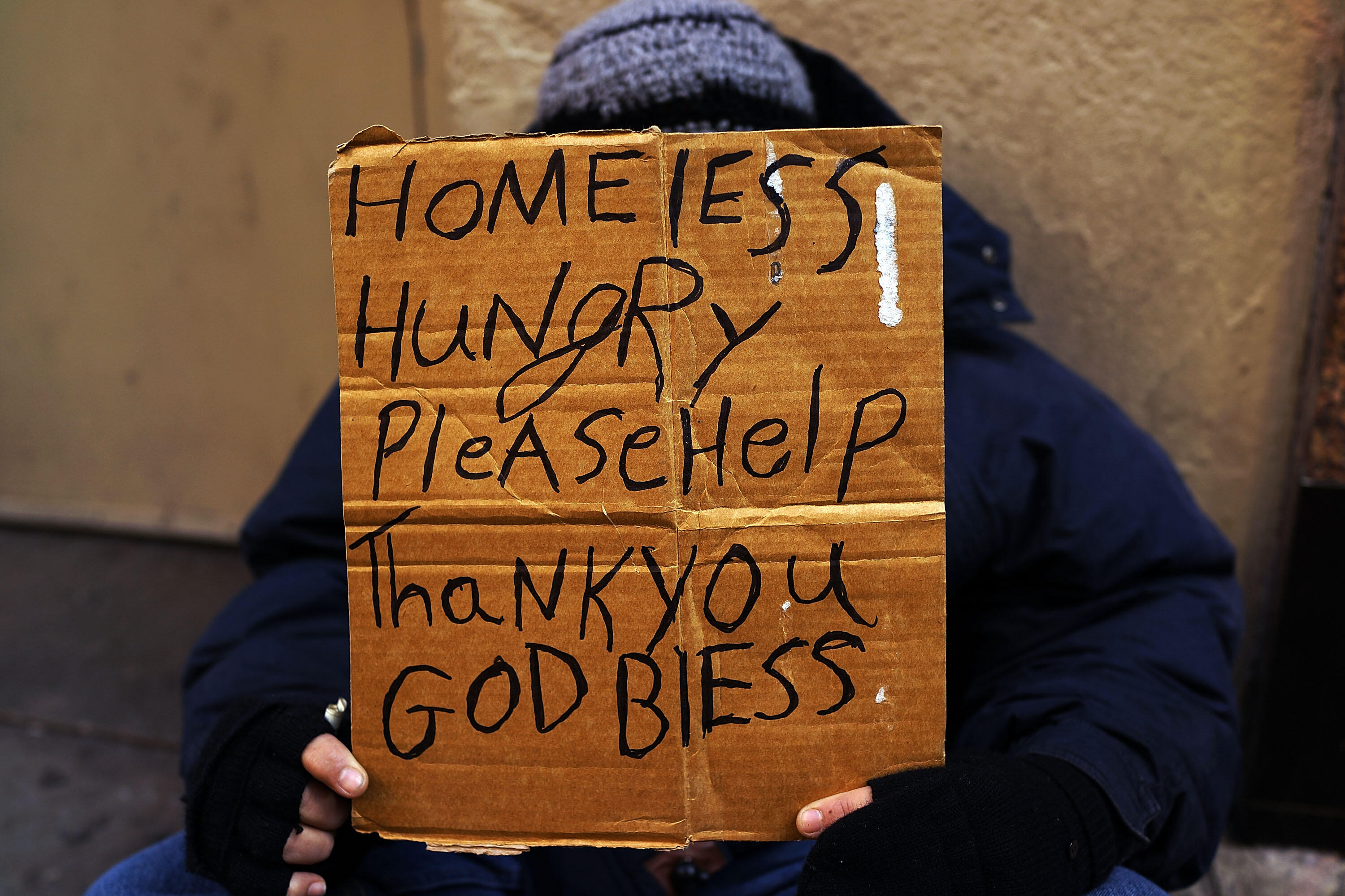 NEW YORK, NY - DECEMBER 04:  A person in economic difficulty holds a homemade sign asking for money along a Manhattan street on December 4, 2013 in New York City.  According to a recent study by the by the United States Department of Housing and Urban Dev