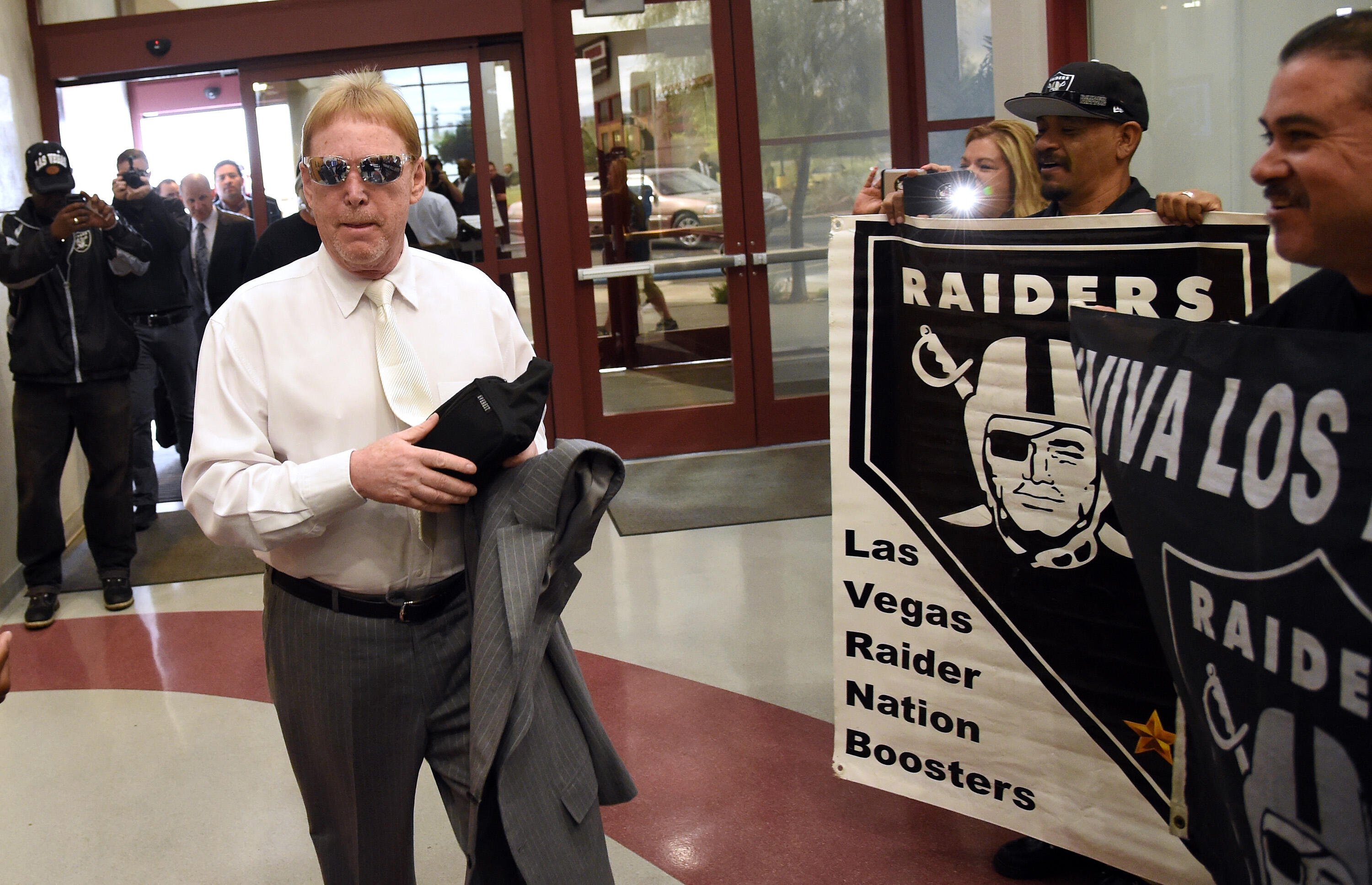 LAS VEGAS, NV - APRIL 28:  Oakland Raiders owner Mark Davis walks past fans holding Raiders signs as he arrives at a Southern Nevada Tourism Infrastructure Committee meeting at UNLV on April 28, 2016 in Las Vegas, Nevada. Davis told the committee he is wi