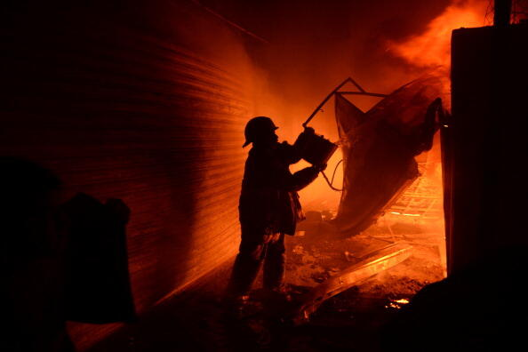 A firegighter tries to douse a fire in La Terminal market on March 25, 2014 in Guatemala City. The disaster left four injured, 50 intoxicated and at least 400 stalls destroyed. AFP PHOTO/Johan ORDONEZ        (Photo credit should read JOHAN ORDONEZ/AFP/Get