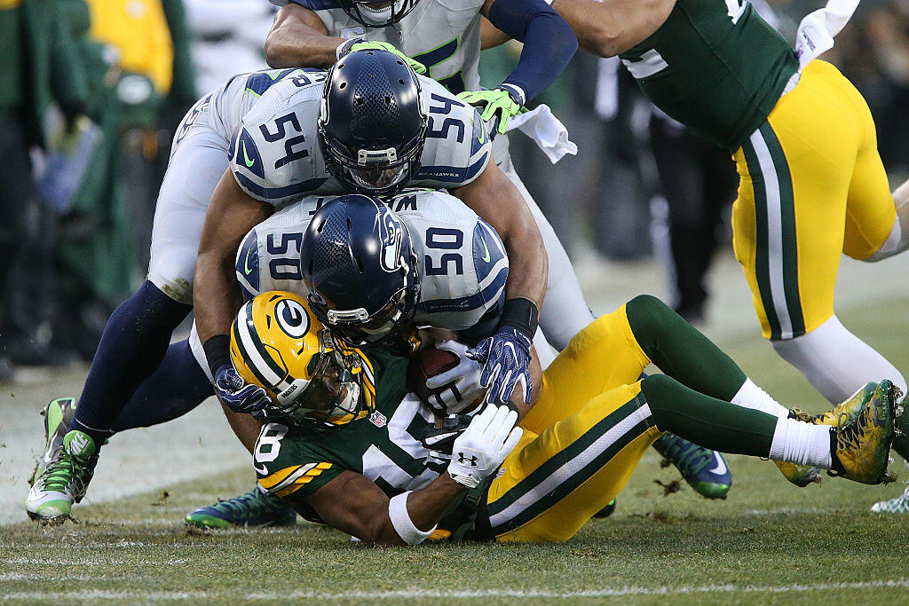 GREEN BAY, WI - DECEMBER 11: Bobby Wagner #54 and K.J. Wright #50 of the Seattle Seahawks tackle Randall Cobb #18 of the Green Bay Packers during the first half of a game at Lambeau Field on December 11, 2016 in Green Bay, Wisconsin.  (Photo by Dylan Buell/Getty Images)