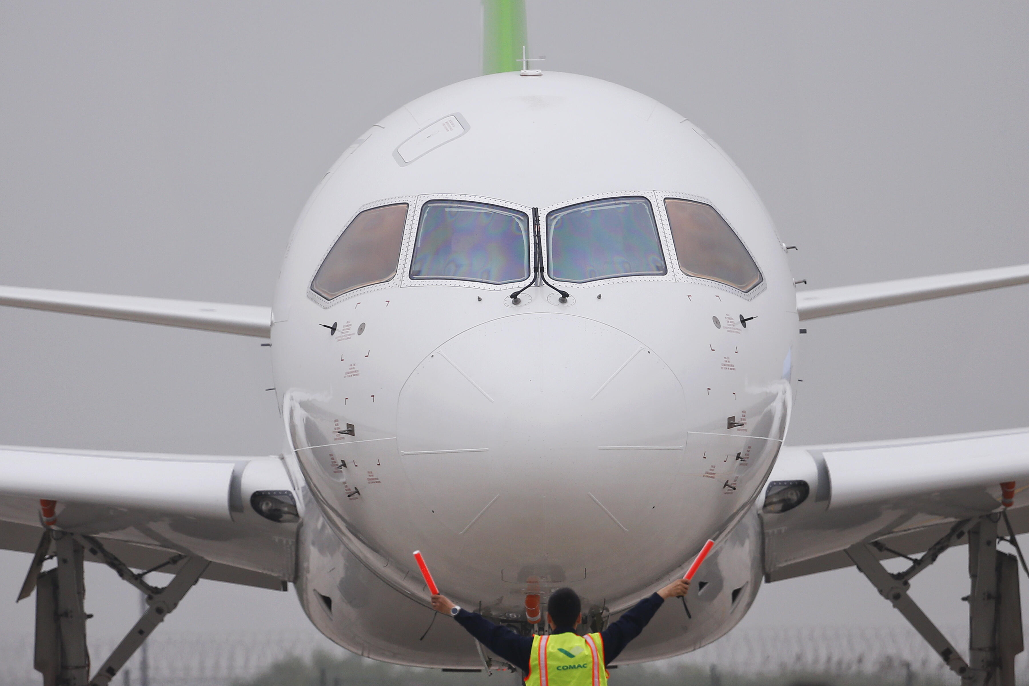 A member of staff signals in front of China's home-grown C919 passenger jet after it landed on its maiden flight at Pudong International Airport in Shanghai on May 5, 2017. The first large made-in-China passenger plane took off on its maiden test flight o