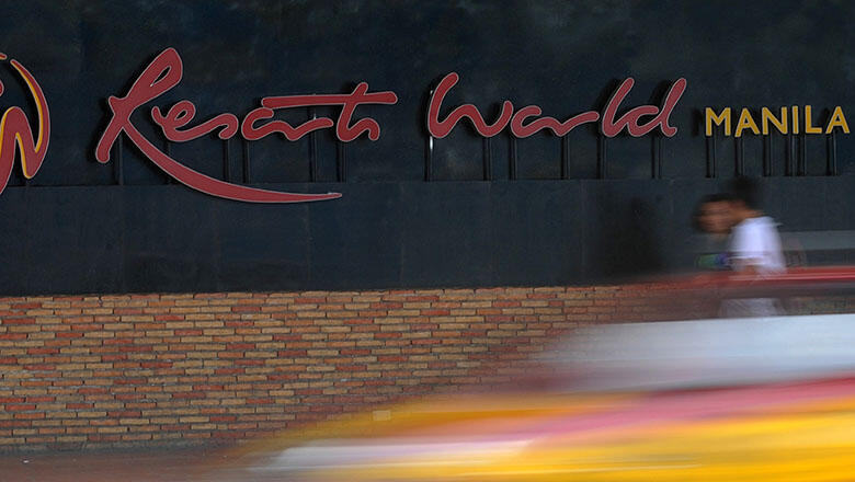 Pedestrians walk in front of Resorts World Manila logo on August 14, 2015. The owner of the Philippines' first mega-casino Resorts World on August 14, said its second-quarter profits halved amid an industry wide slump that could threaten the country's bid