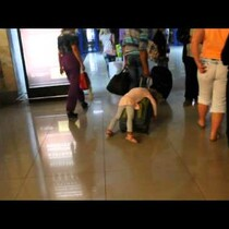 AWWWW!  Girl Sleeps On Dad's Suitcase As He Pulls It Through The Airport