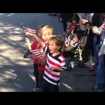 Little boy salutes soldiers and thanks them at parade