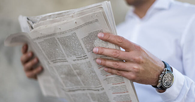 man reading newspaper news media generic stock