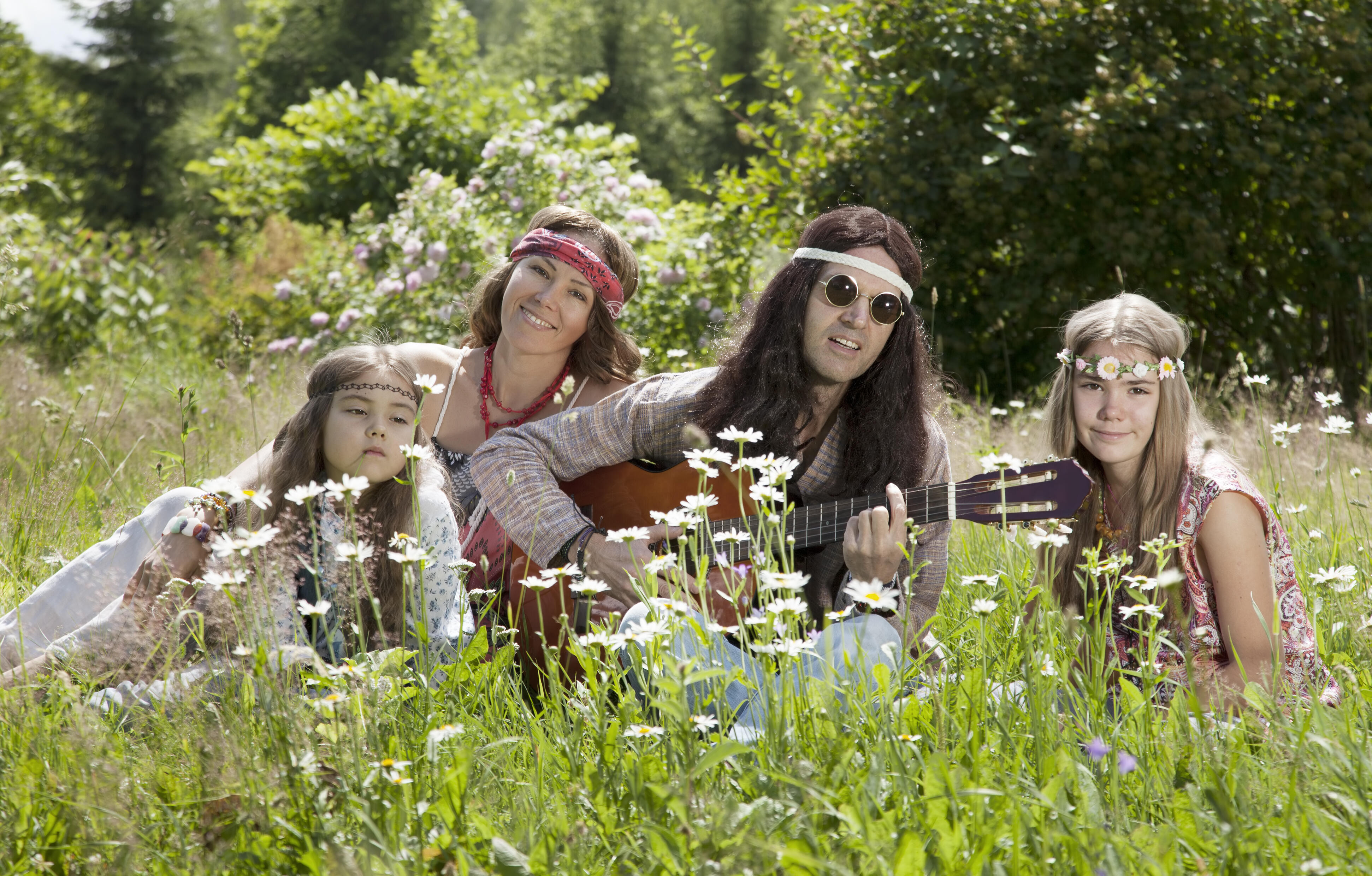 Hippie family sitting in the field and playing guitar on a sunny summer day.