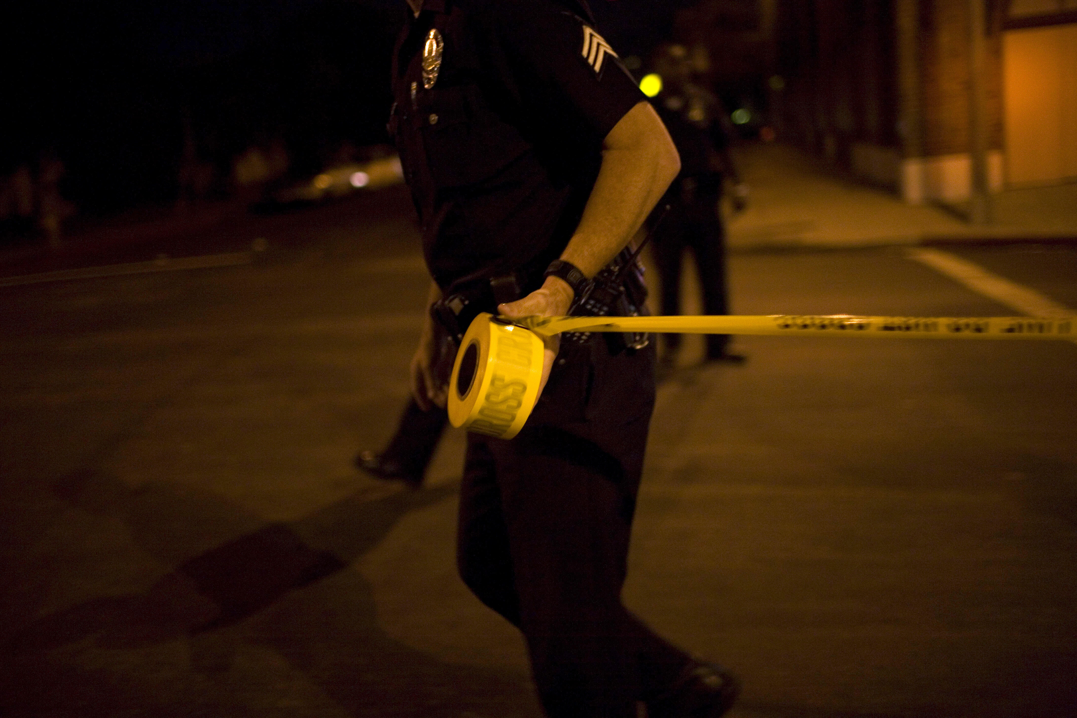 LOS ANGELES - SEPTEMBER 14: Los Angeles Police Department gang unit officers tape off a Crime Scene Investigation area following the shooting of a man September 14, 2007 in the Northeast precinct of Los Angeles, California. The injured man was taken to a