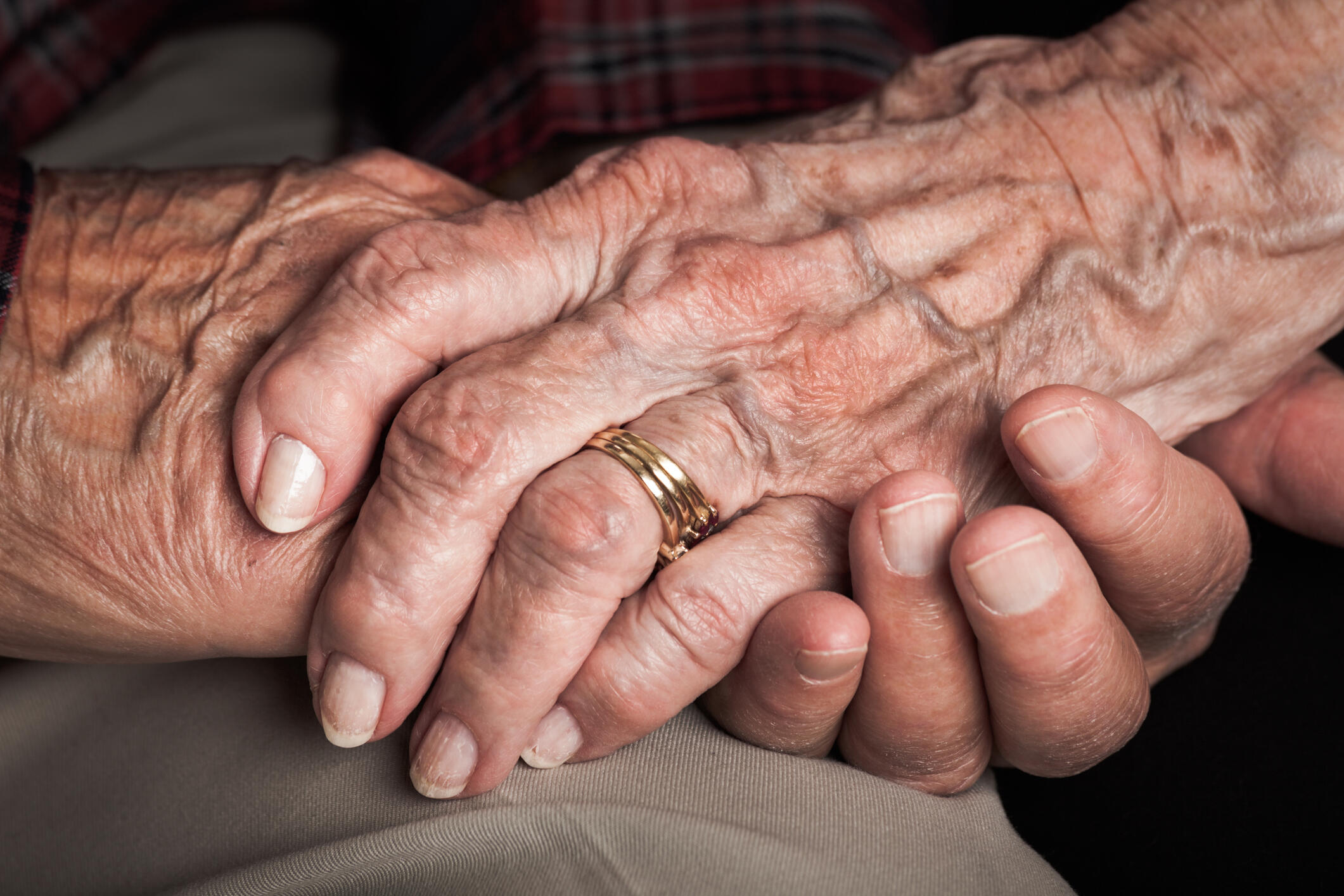Senior married couple holding hands: sixty years of faithfulness. Closeup of hands only.