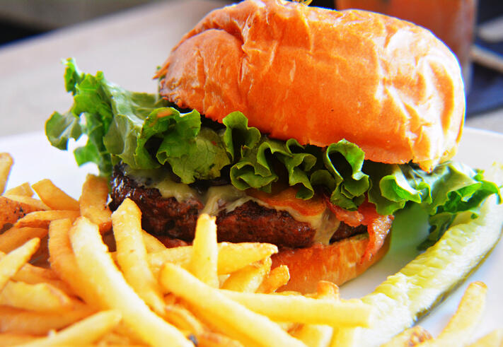 Close-Up Of Fresh Hamburger And French Fries Served On Table At Restaurant