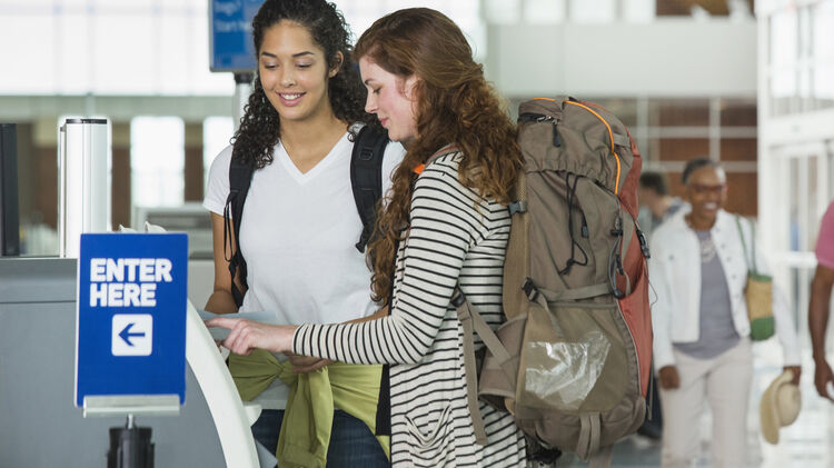 Women checking in at airport kiosk