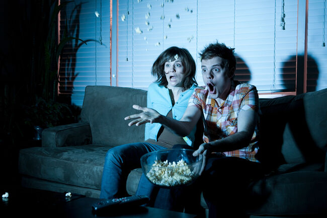 Young couple watching tv, man throwing popcorn