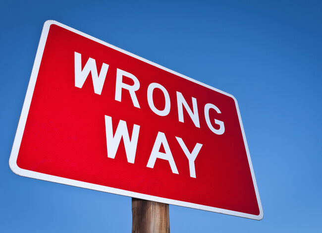Wrong way sign against blue sky