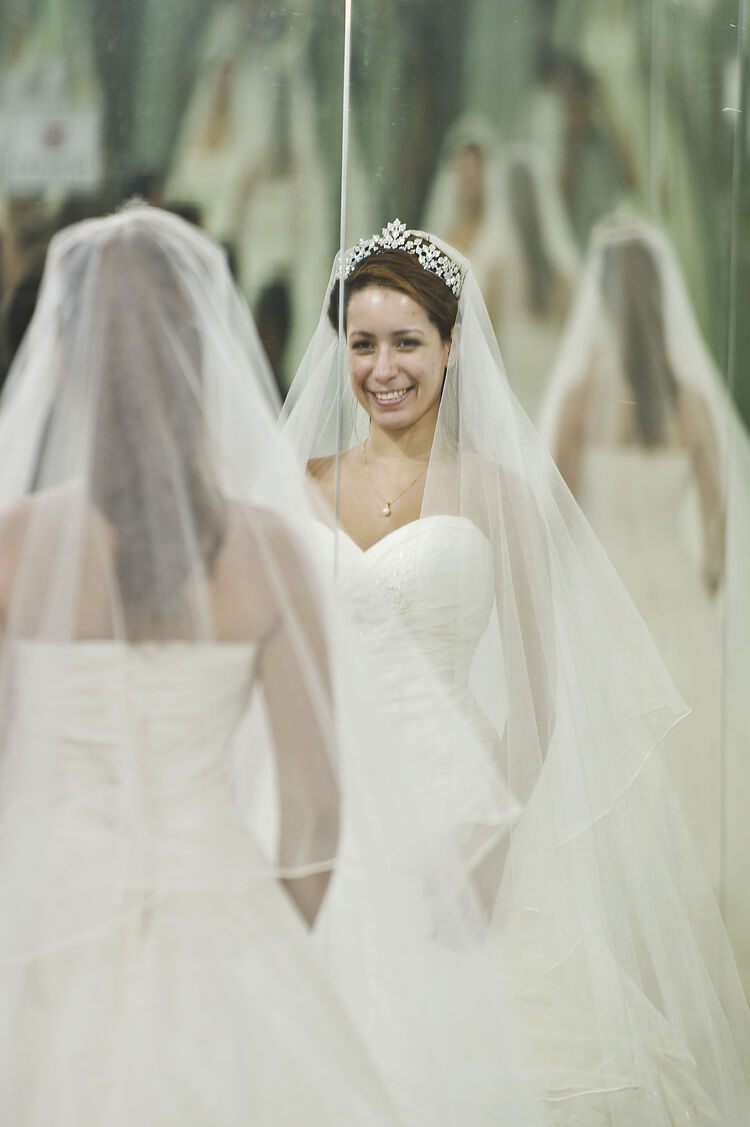 A woman tries on a wedding dress in a br