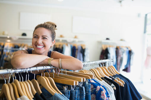 Portrait enthusiastic woman in clothing shop