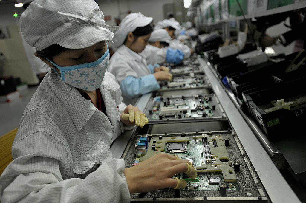 In a picture taken on May 26, 2010 Chinese workers assemble electronic components at the Taiwanese technology giant Foxconn's factory in Shenzhen, in the southern Guangzhou province. Foxconn on June 2 confirmed the death of another employee but denied he