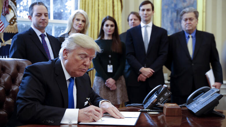 WASHINGTON, DC - JANUARY 24: President Donald Trump signs one of five executive orders related to the oil pipeline industry in the Oval Office of the White House January 24, 2017 in Washington, DC. Looking on are White House Chief of Staff Reince Priebus,