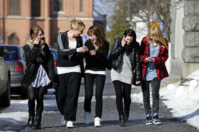Teenagers use their cell phones after sc