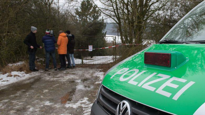 A police car and journalists stand in front of the fence blocking the access to the private property where six teenagers were found dead in Arnstein, central Germany, on January 30, 2017. Six teenagers were found dead Sunday after holding a party in a gar