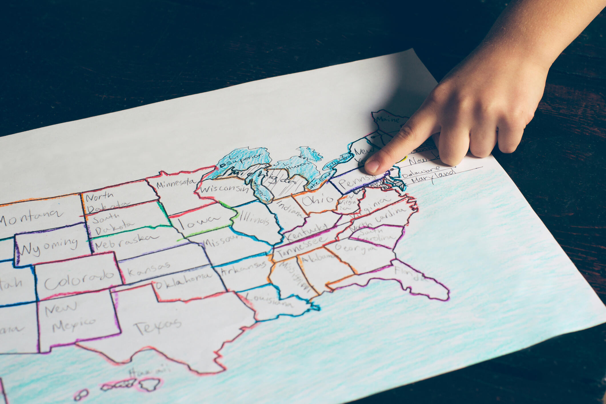 A child's finger pointing to a hand drawn map of the United States of America.