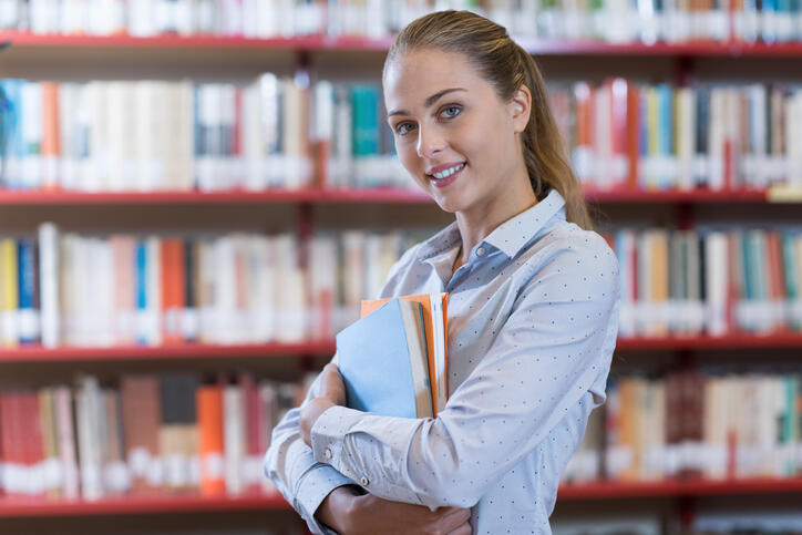 Confident student girl posing at the library, she is smiling and holding books, bookshelves on the background