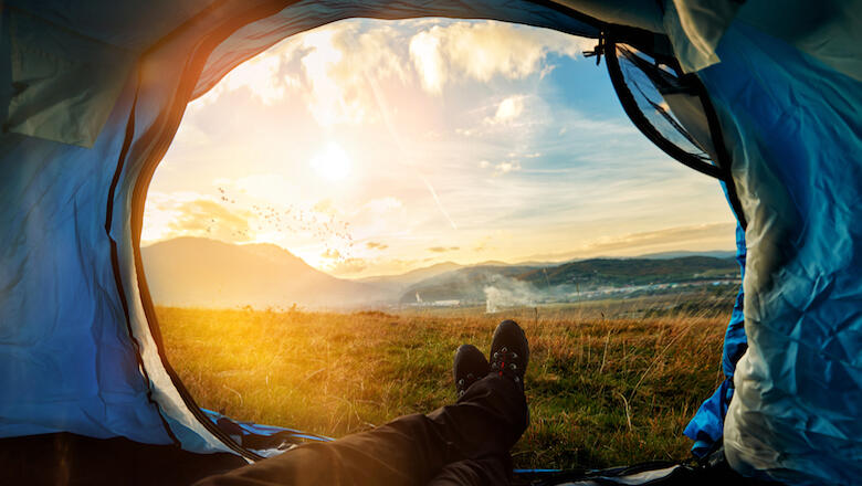 personal perspective of hiker in his tent resting, looking at the sunset and taking a break.
