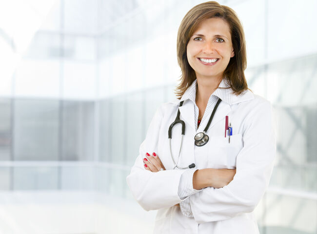 Female doctor standing and smiling with her arms crossed