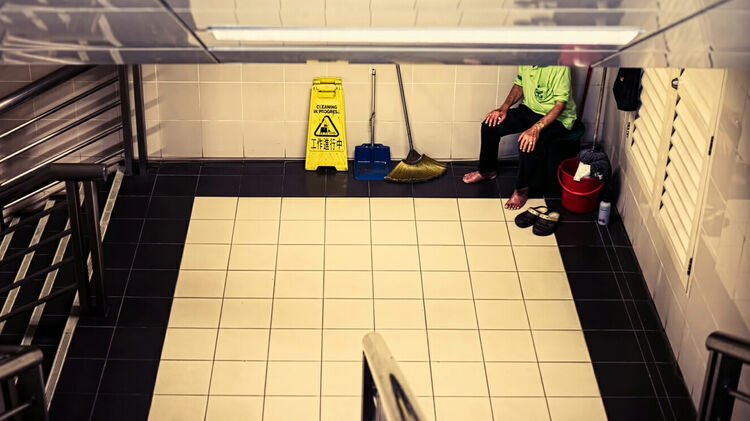 Low Section Of A Janitor Sitting At The Room Corner