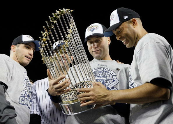 NEW YORK - NOVEMBER 04:  (L-R) Andy Pettitte #46, Jorge Posada #20, Derek Jeter #2 and Mariano Rivera #42 of the New York Yankees celebrate with the trophy after their 7-3 win against the Philadelphia Phillies in Game Six of the 2009 MLB World Series at Y