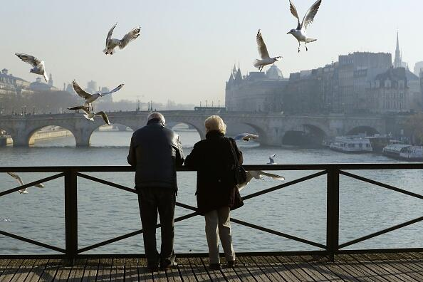 An elderly couple watches sea gulls flying over the Pont des Arts that crosses the River Seine in central Paris on December 1, 2016.  / AFP / PATRICK KOVARIK        (Photo credit should read PATRICK KOVARIK/AFP/Getty Images)
