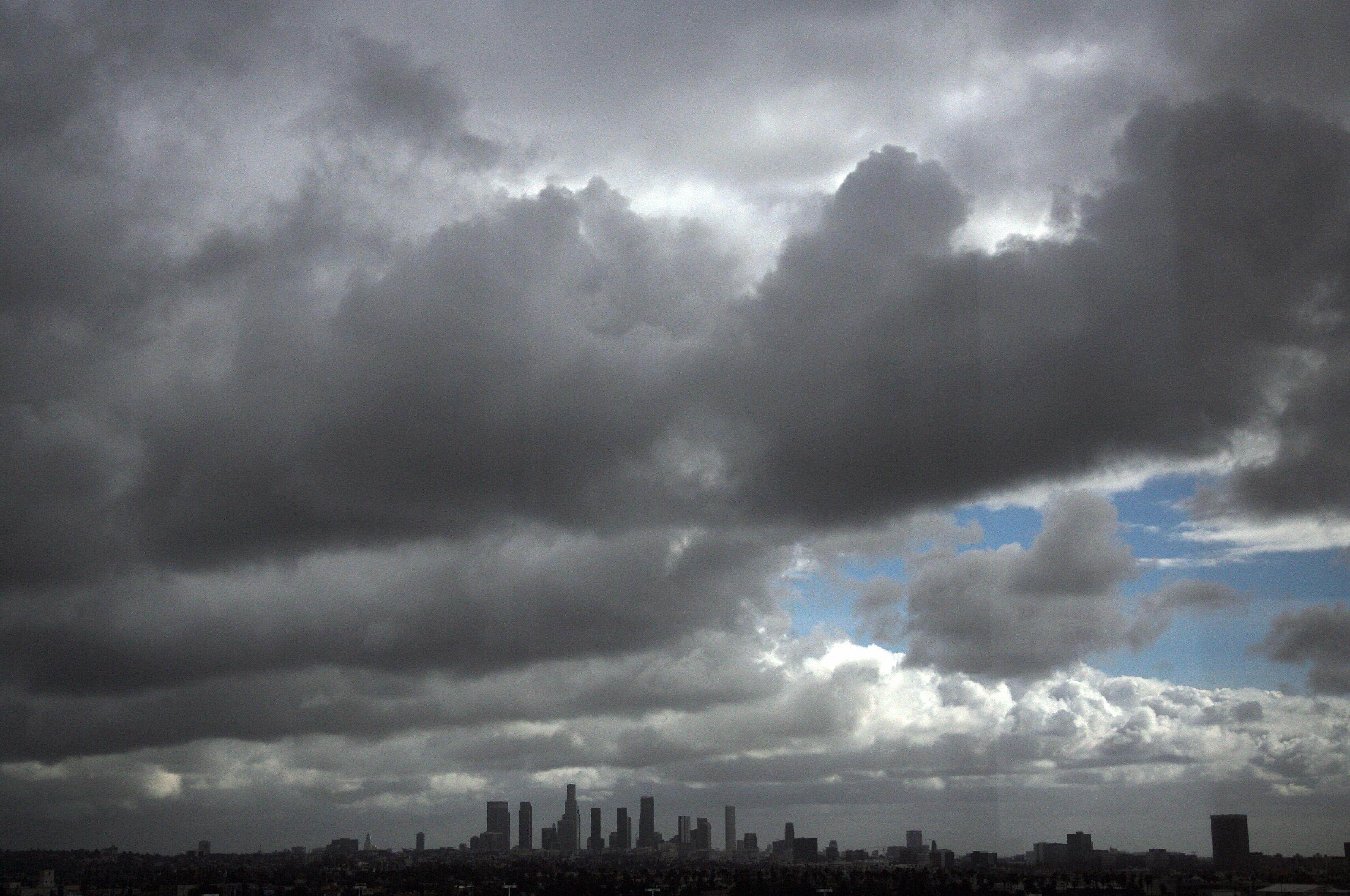 Storm clouds pass over the downtown Los Angeles skyline as the sun breaks through the thick clouds early  07 December 2007. Forecasters say urban areas can expect an inch of rain. AFP PHOTO GABRIEL BOUYS (Photo credit should read GABRIEL BOUYS/AFP/Getty I
