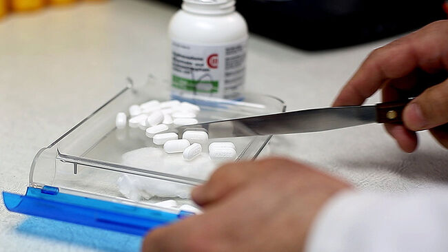 A pharmacist counts pain medication at a South Portland Pharmacy Thursday, Feb. 19, 2014. With the s