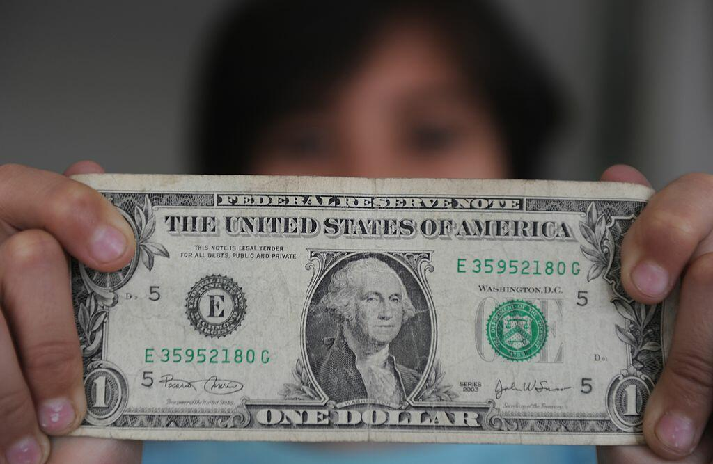 A person holds a one dollar bill on December 18, 2011 in San Jose, Costa Rica. Apart of the local currency, colones, dollars are also used in Costa Rica. AFP PHOTO/ Rodrigo ARANGUA (Photo credit should read RODRIGO ARANGUA/AFP/Getty Images)