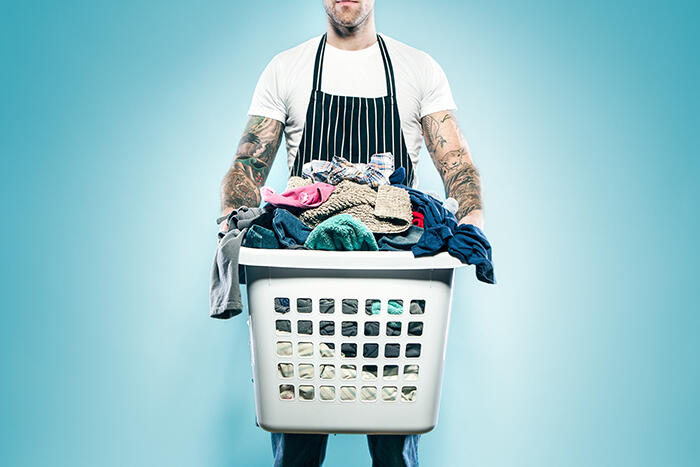 A man with tattoo sleeves on both of his arms wears an apron and holds a full laundry basket of dirty clothes ready to be washed.  Could be single guy, father, husband; whatever the case, he's not afraid to help out with domestic chores around the home.