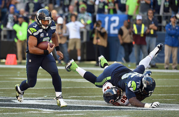 SEATTLE, WA - SEPTEMBER 27:  Quarterback Russell Wilson #3 of the Seattle Seahawks runs with the ball as tackle Russell Okung #76 of the Seattle Seahawks blocks defensive line man Ego Ferguson of the Chicago Bears during the third quarter of the game at CenturyLink Field on September 27, 2015 in Seattle, Washington.  (Photo by Steve Dykes/Getty Images)