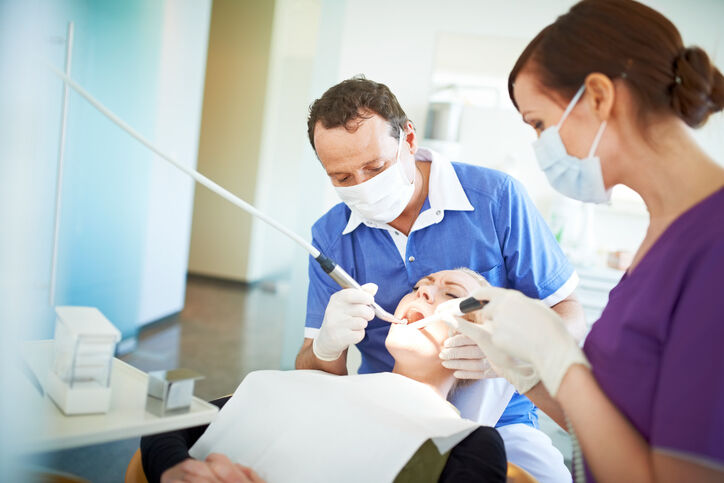 Dentist operating on a patient in pain