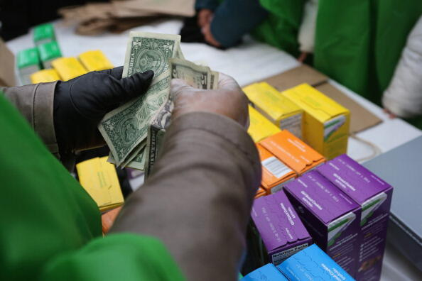 NEW YORK, NY - FEBRUARY 08:  MOney is collected as Girl Scouts sell cookies while a winter storm moves in on February 8, 2013 in New York City. The scouts did brisk business, setting up shop in locations around Midtown Manhattan on National Girl Scout Coo