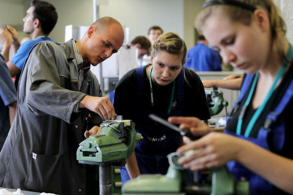 BERLIN - SEPTEMBER 01:  An instructor teaches mechanical engineering trainees the basics of precision filing at the Siemens training center on September 1, 2010 in Berlin, Germany. Approximately 320 trainees are beginning this year's program at Siemens, w
