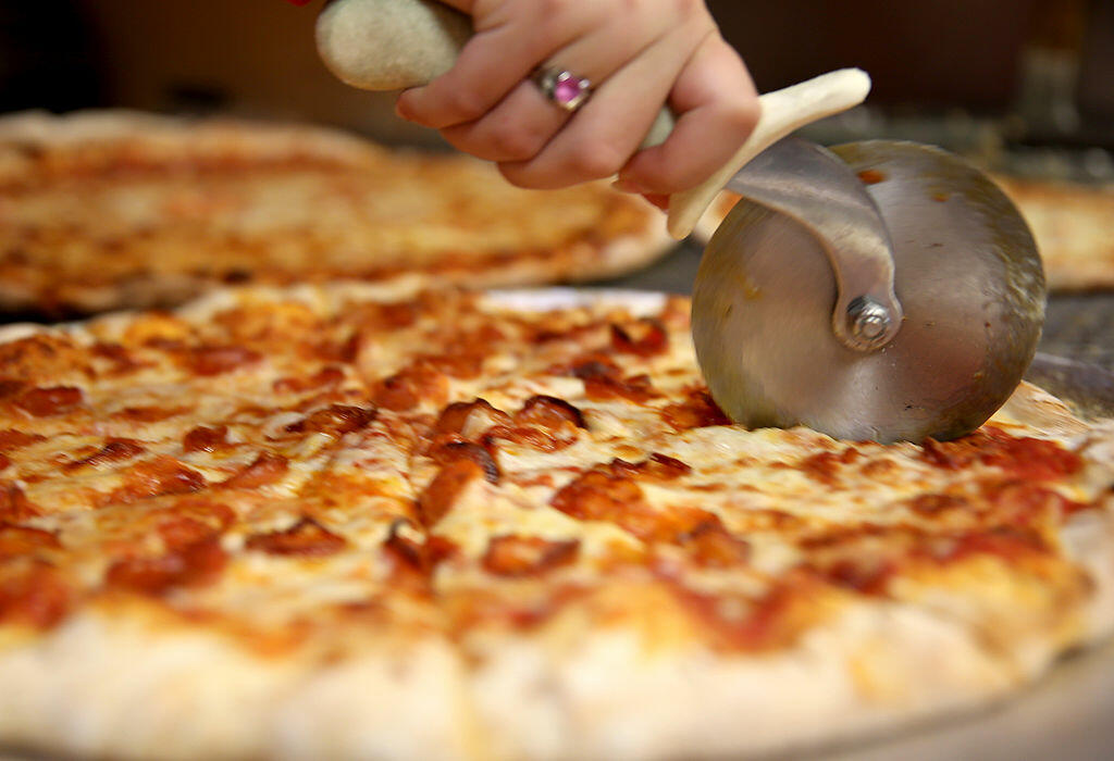 CORAL GABLES, FL - SEPTEMBER 12:  Arlet Lagoa cuts a pizza into slices at Miami's Best Pizza restaurant on September 12, 2014 in Coral Gables, Florida. Reports indicate that milk futures have risen to a record as exports by the U.S. have climbed amid shri