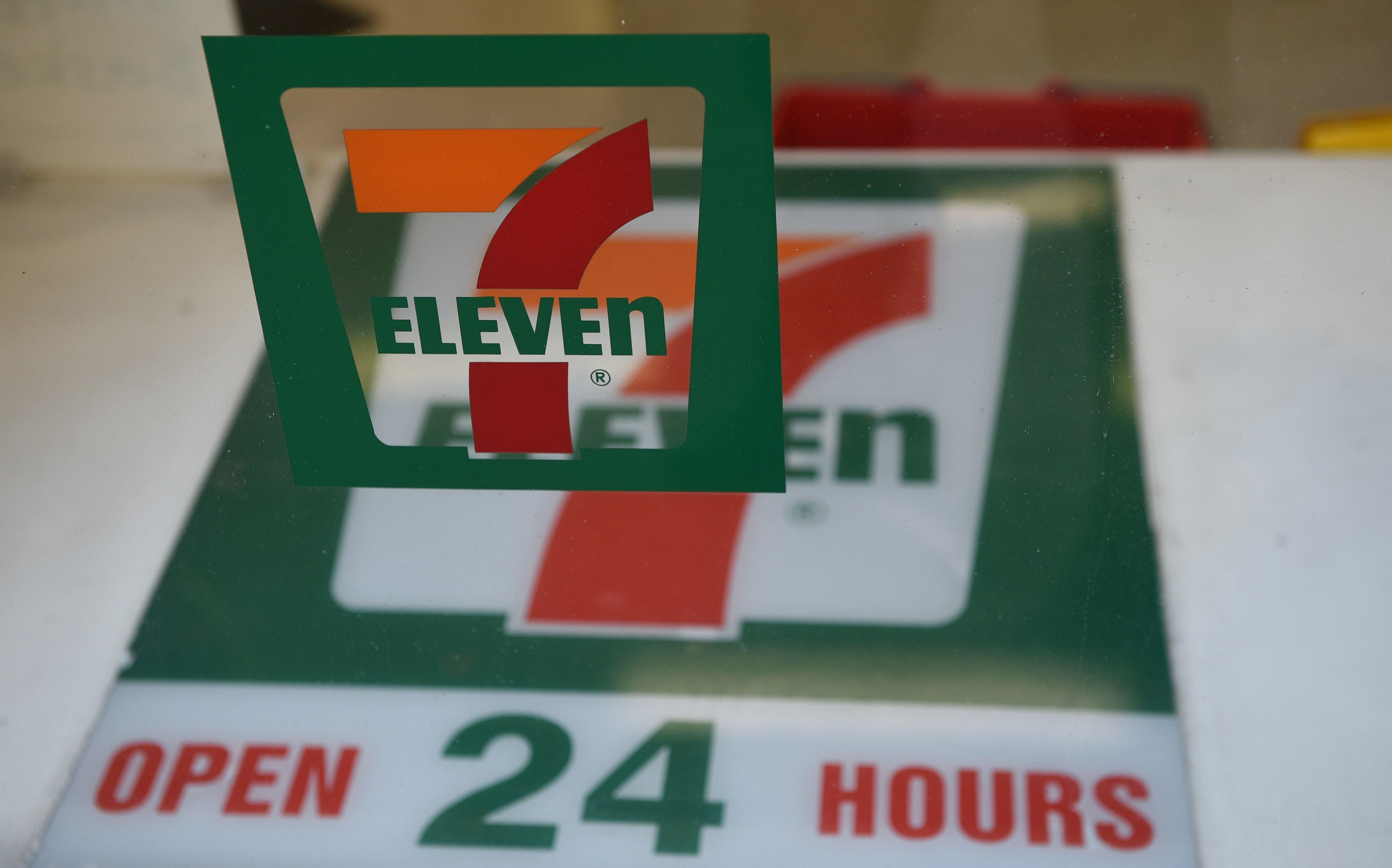 A sign for a 7-Eleven convenience store is seen at a store in Sydney on September 1, 2015. The convenience store giant will establish an independent panel to review damaging allegations that its franchisees doctored payrolls and systematically underpay wo