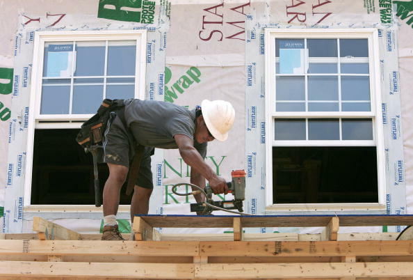 A construction worker uses his nail-gun