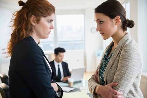 Businesswomen glaring at each other in office