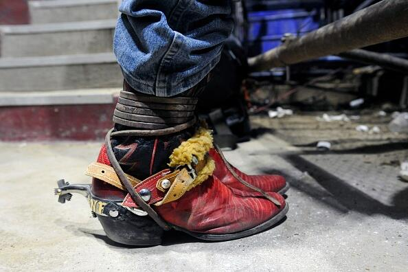 A professional bull rider wearing cowboy boots with spurs waits to compete in the bull riding finals of the