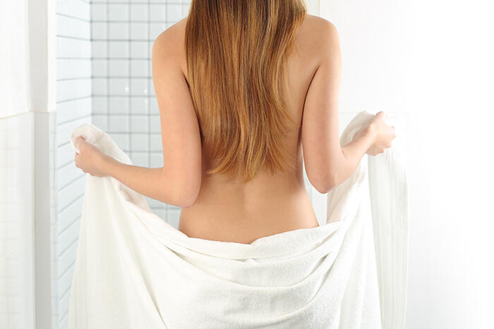 Back view of a woman body entering in the shower with a white towel