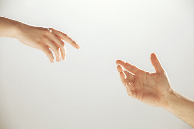 Hands reaching towards each other