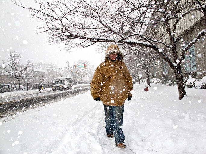 Man in a warm jacket walking on a sidewalk of a city during snowstorm.