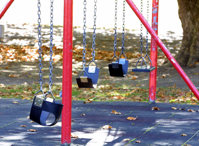 Childrens swings are empty at a local childrens pl