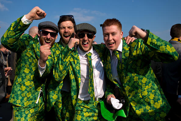 CHELTENHAM, ENGLAND - MARCH 17: Racegoers pose for photographs wearing shamrock covered suits during St Patrick's Day at the Cheltenham Festival at Cheltenham Racecourse on March 17, 2016 in Cheltenham, England. The four day annual jump racing event sees jockeys compete for a piece of the 4.1 million GBP of the prize money.  (Photo by Ben Pruchnie/Getty Images)